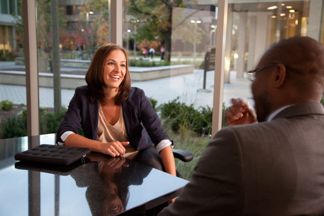 female graduate student in business clothes talking to a man seated across from her