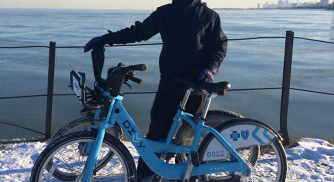 Alvaro Villagran dressed in winter bike riding gear with divvy bike