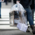 person walks down street with retail shopping bag