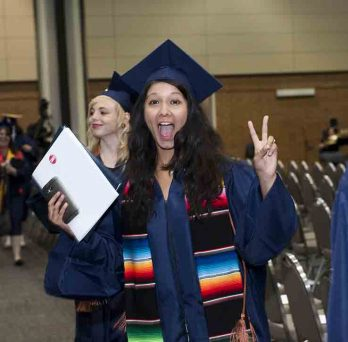 Graduate showing peace sign.