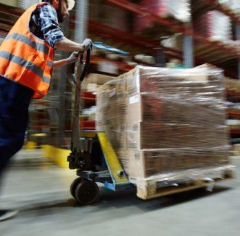 Warehouse employee pushing a cart.